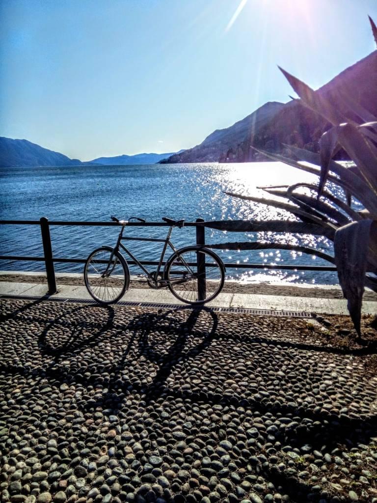 lago azzurro sullo sfondo, bicicletta in primo piano, veduta in profondità dell'orizzonte. Agave in primo piano.