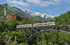 Panorama alpino sullo sfondo, ponte ferroviario e treno.