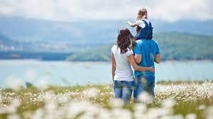 famiglia felice che passeggia ai bordi de lago