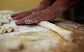 tavolo da cucina infarinato con mani che impastano