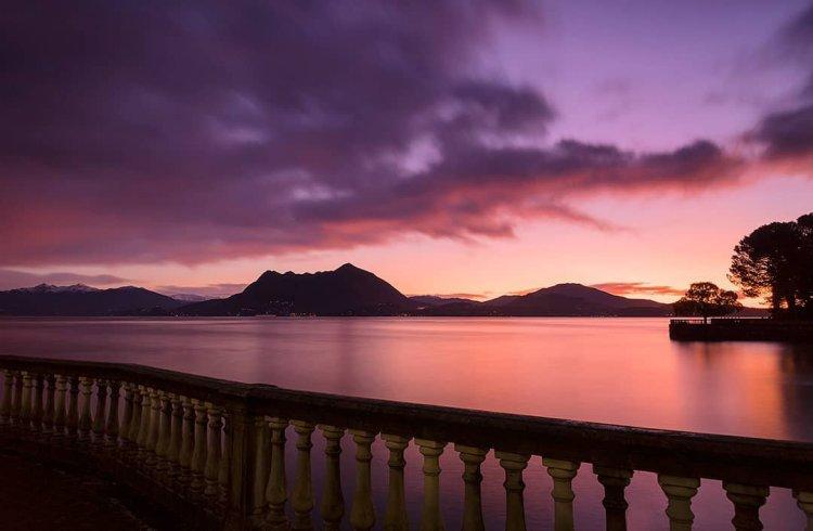balconata su lago, tramonto dai colori viola rosa e arancio. montagne sullo sfondo