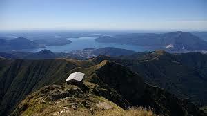 paesaggio alpino, basita e lago in primo piano.