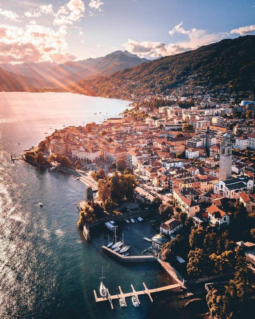Citta di Pallanza veduta aerea, molo delle barche, monumento dei caduti. luce del mattino che illumina il paese ed il lago.