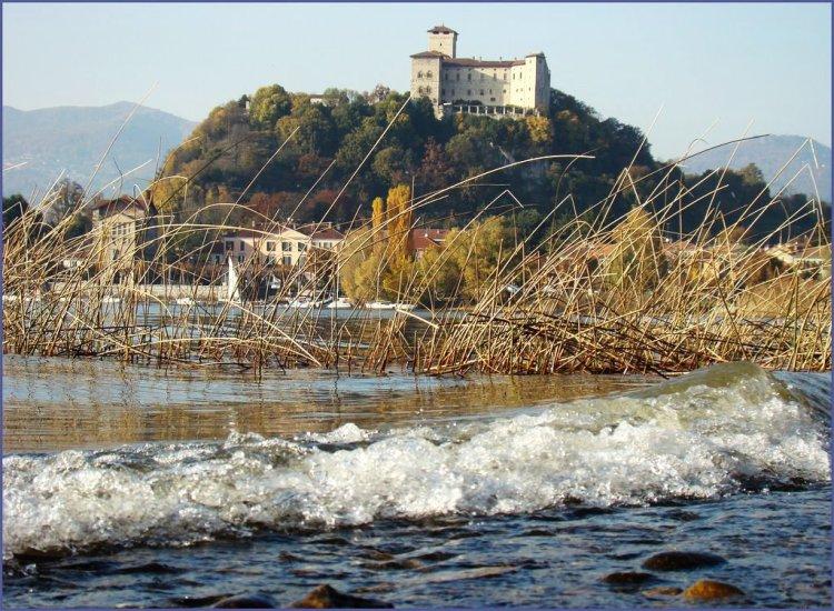 onde del lago che battono sulla battigia. canneto. castello di angera in cima alla verde rocca borromea